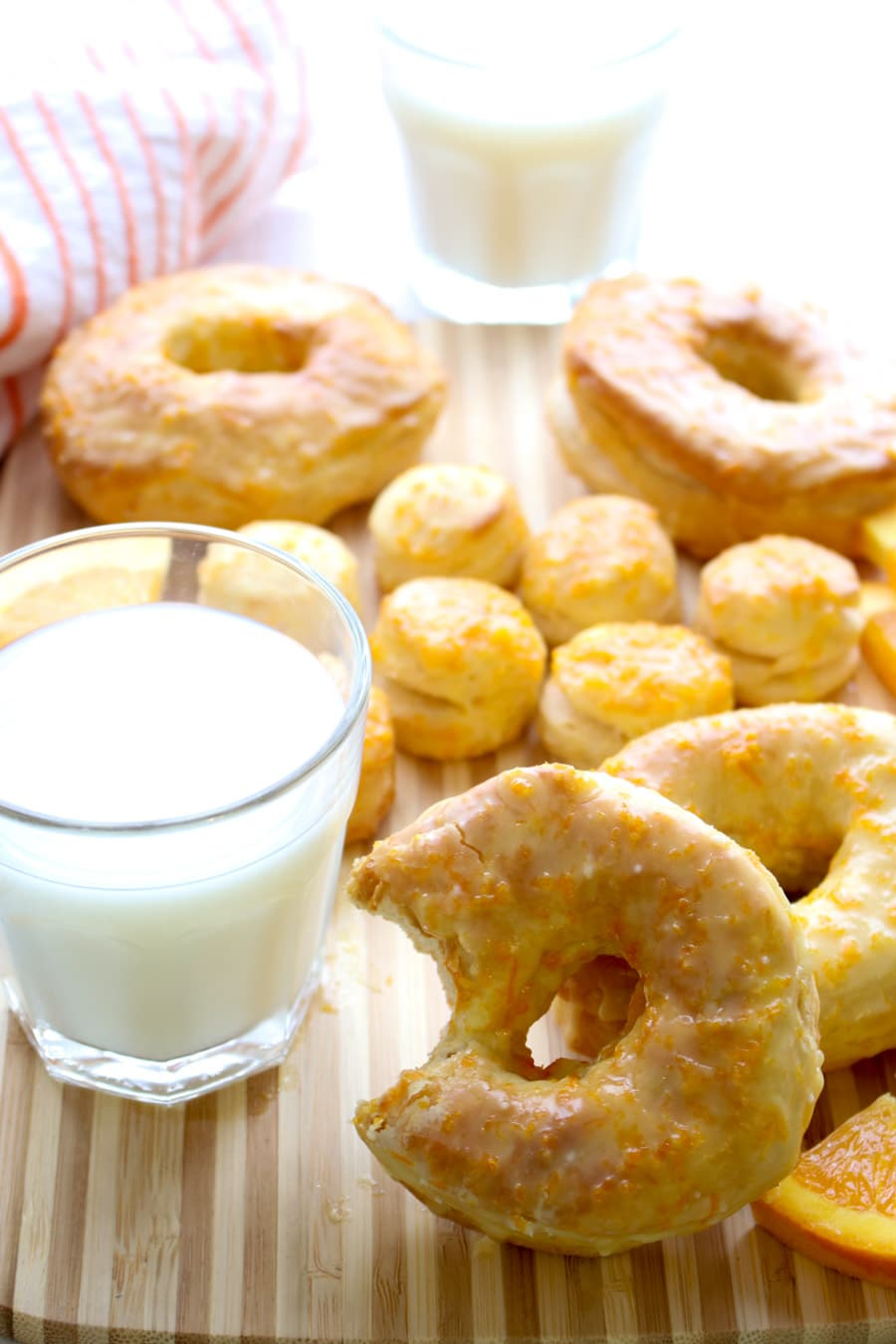 A donut with a bite out leaning against a glass of milk
