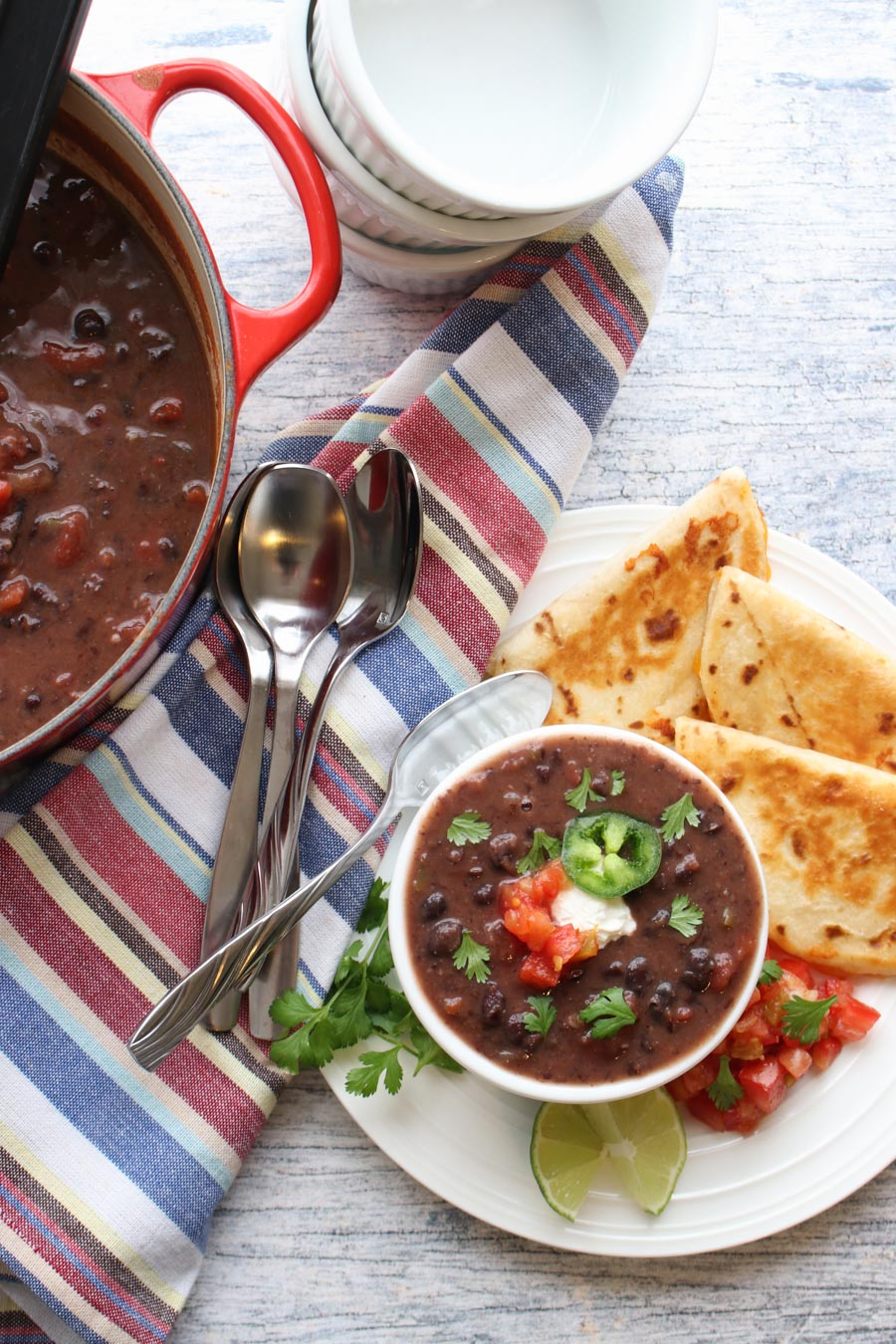 black bean soup in a pot and a bowl with quesadillas on the side