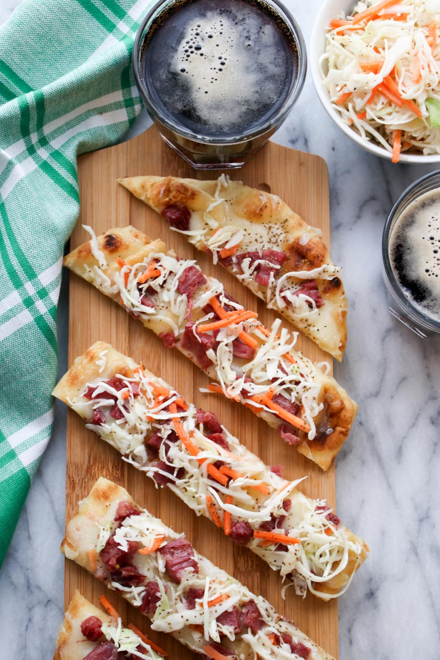 Corned beef flatbread on a wood board, with a bowl of slaw and two dark beers