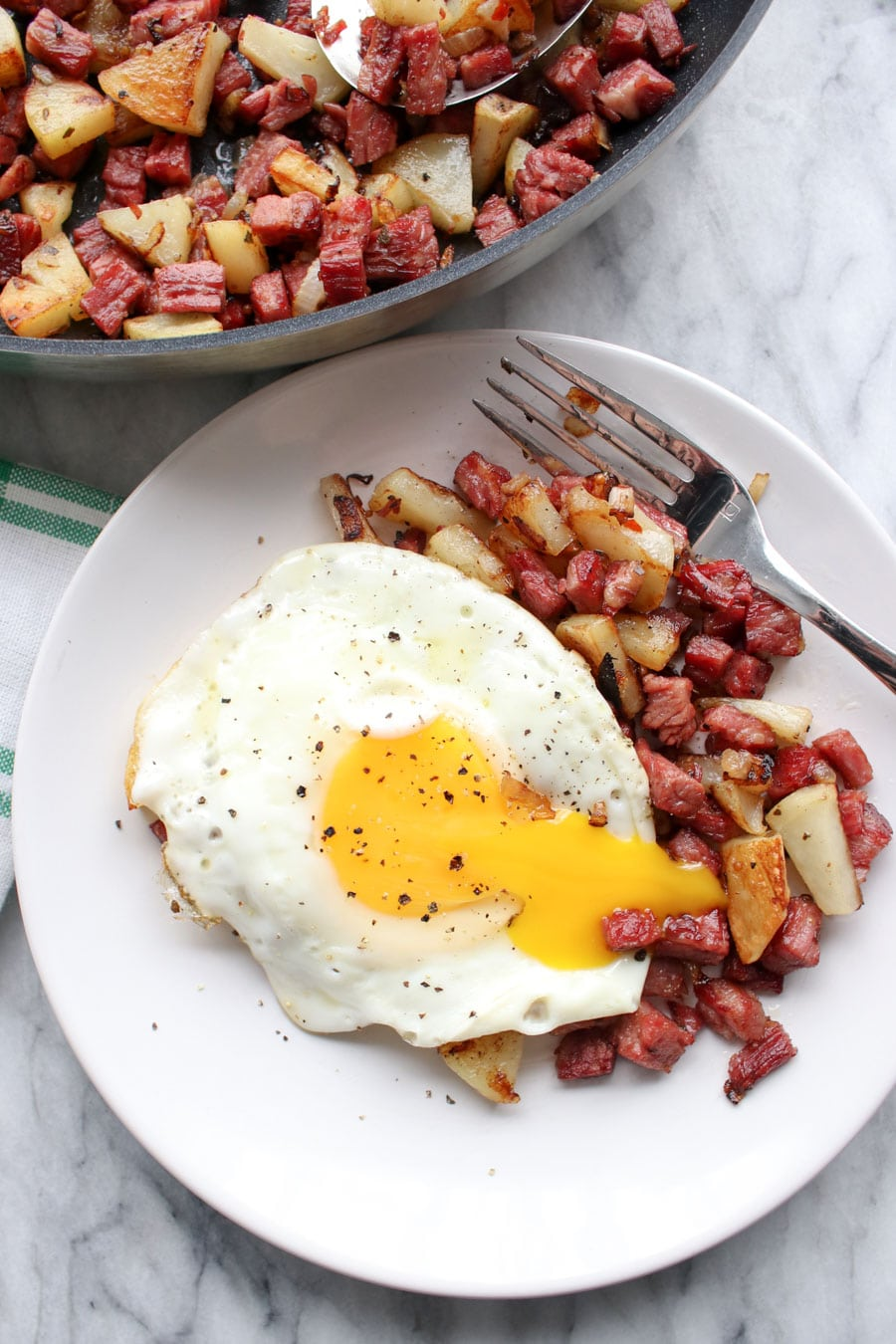 Plate of hash with a broken sunny side up egg on top