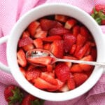 A bowl red strawberries sitting on a pink and white cloth