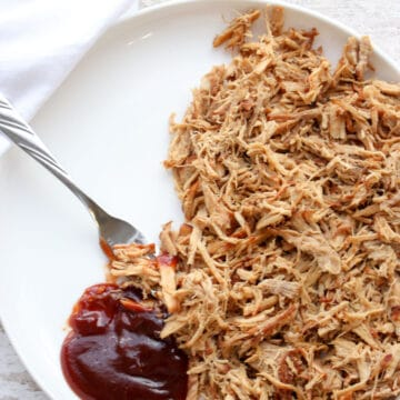 Pulled pork on a white plate with a dollop of BBQ sauce