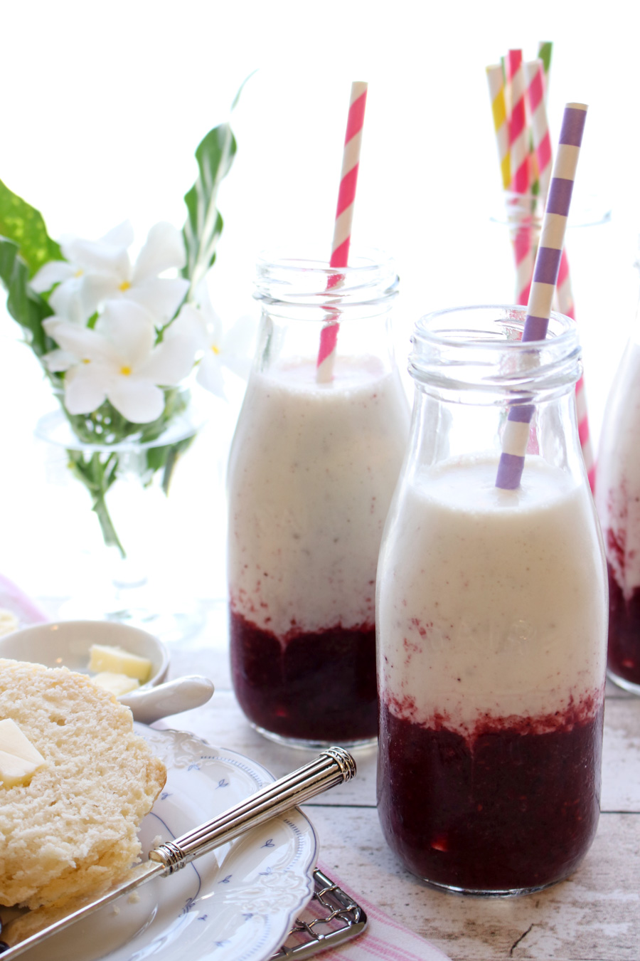 BANANA BERRY YOGURT SMOOTHIE WITH BISCUITS AND BUTTER AND FLOWERS IN THE BACKGROUND