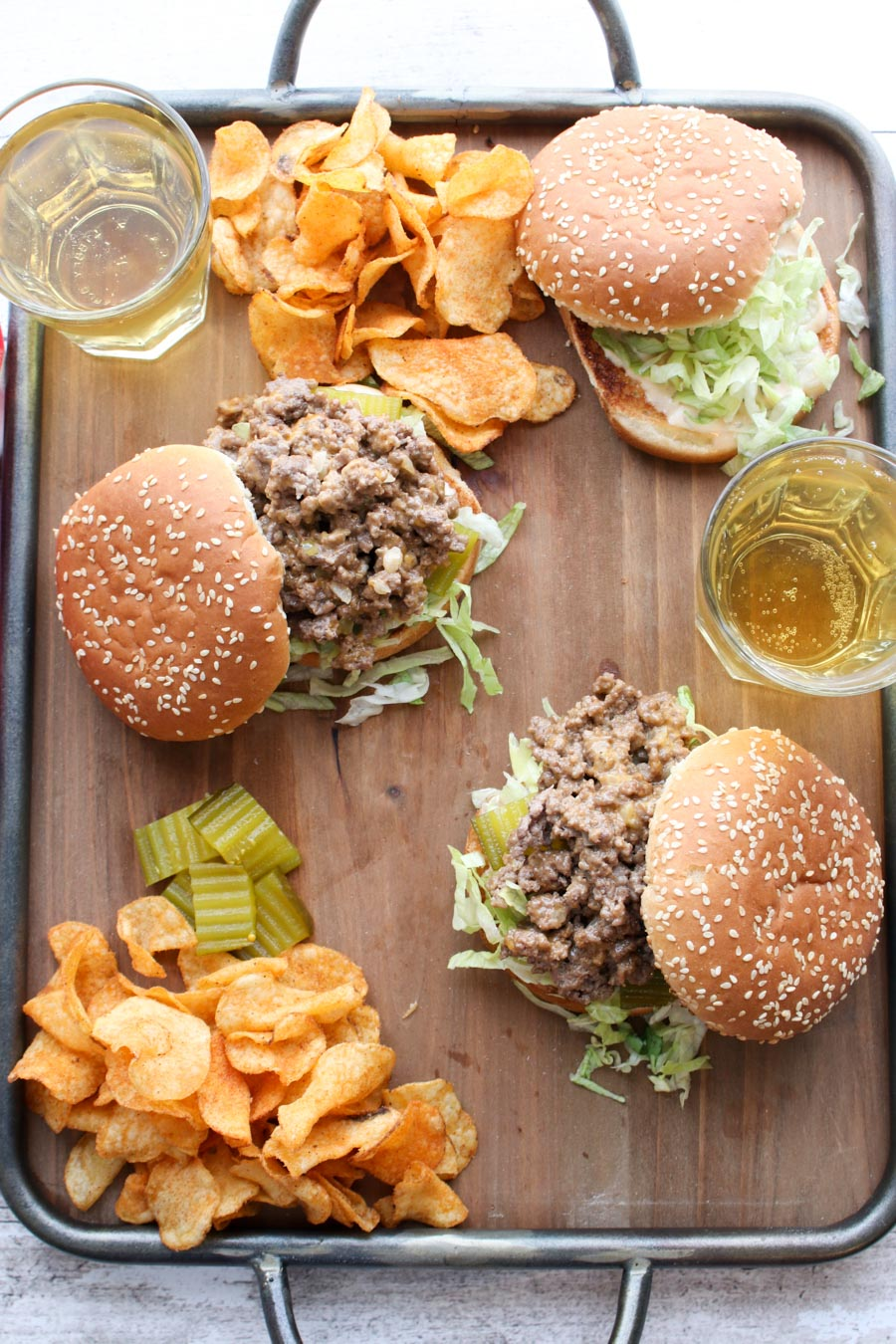 Overhead shot of sloppy joe sandwiches with chips and beer on a try