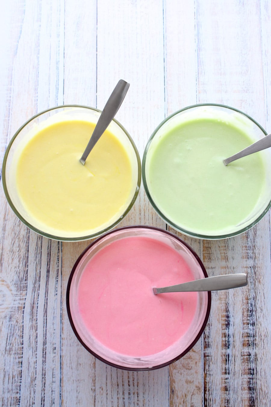 three different colors of cake mix - yellow, green, pink