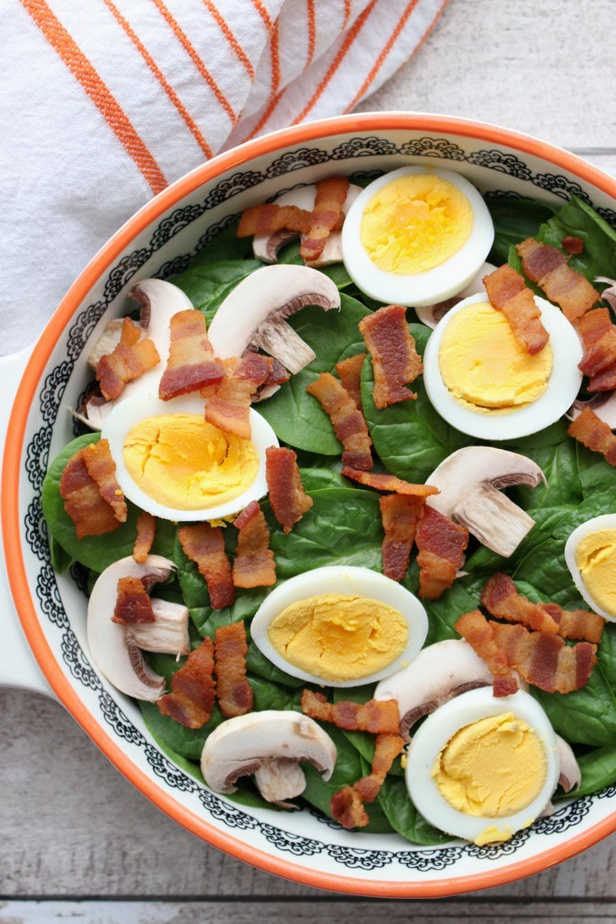 Bowl of spinach with mushrooms, eggs, bacon