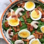 Bowl of spinach salad with eggs, mushrooms, and bacon