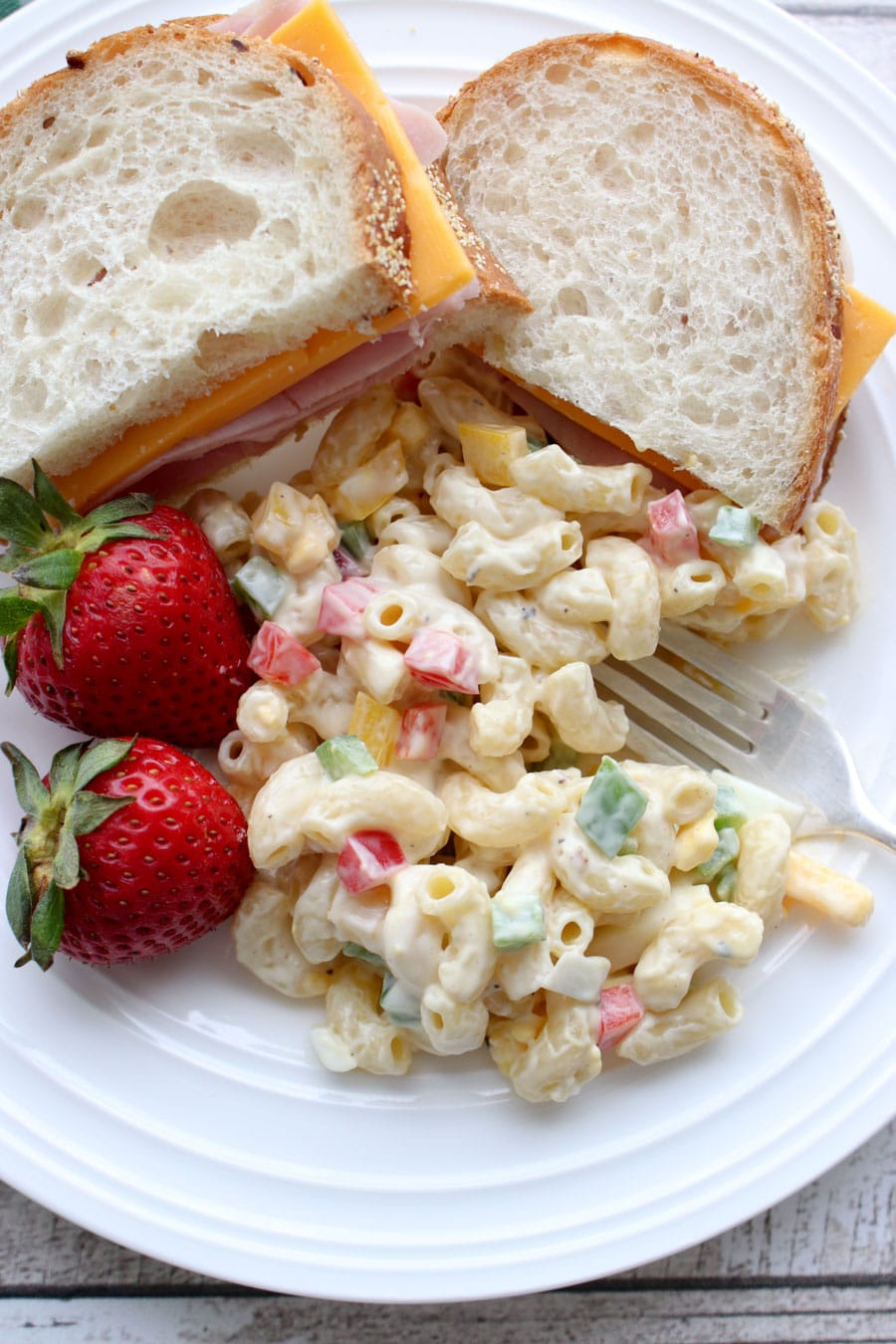 Scoop of macaroni salad on a plate with a sandwich and strawberries