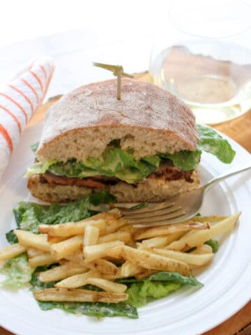 Sandwich and fries on a plate with a glass of white wine in background
