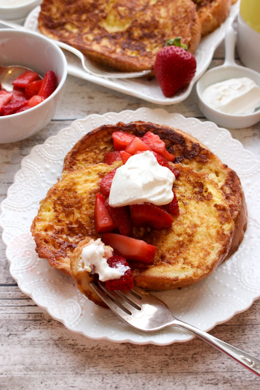 Slice of french toast on a plate with strawberries and cream