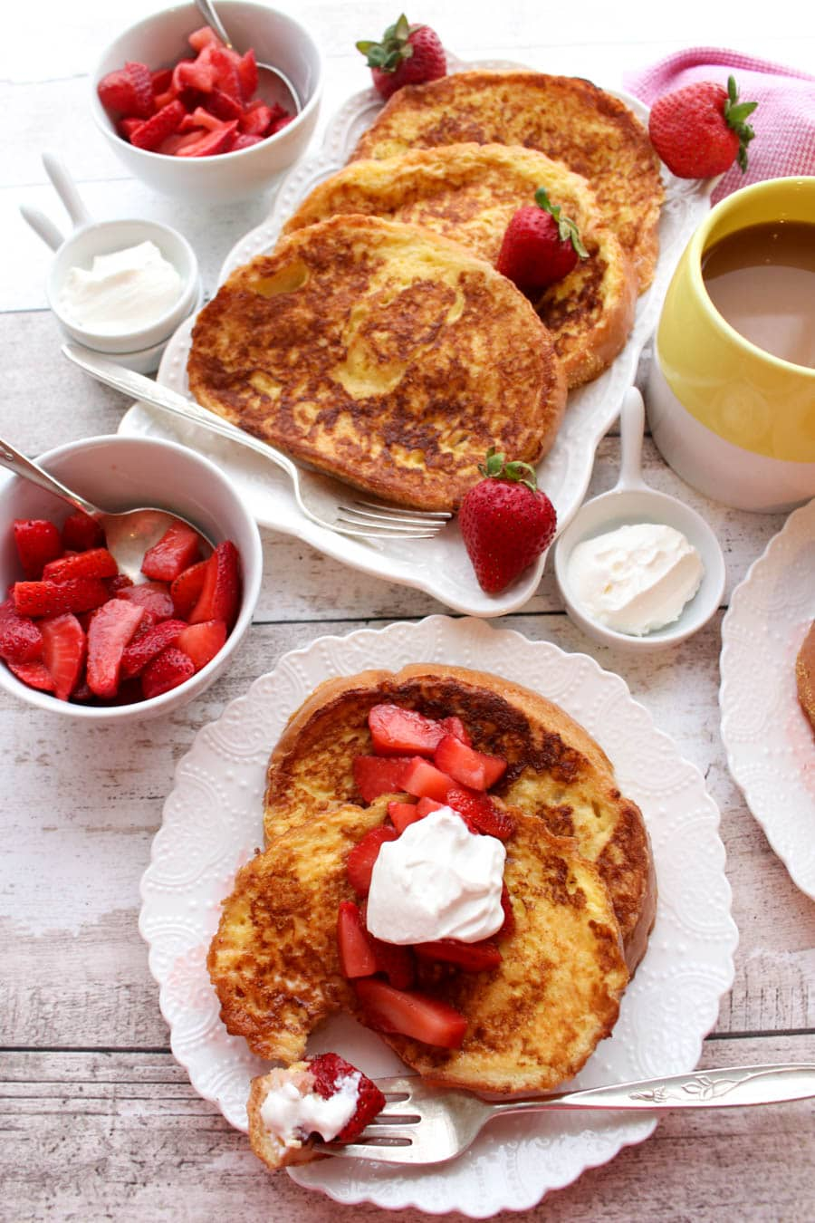 Platter and plates of french toast with strawberries and sour cream