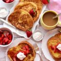 Platter and plates of french toast with strawberries and cream