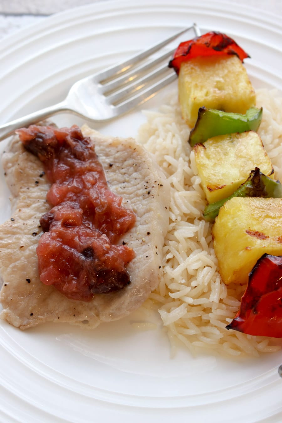 Pork chop topped with chutney. Rice and fruit kabob on the side.