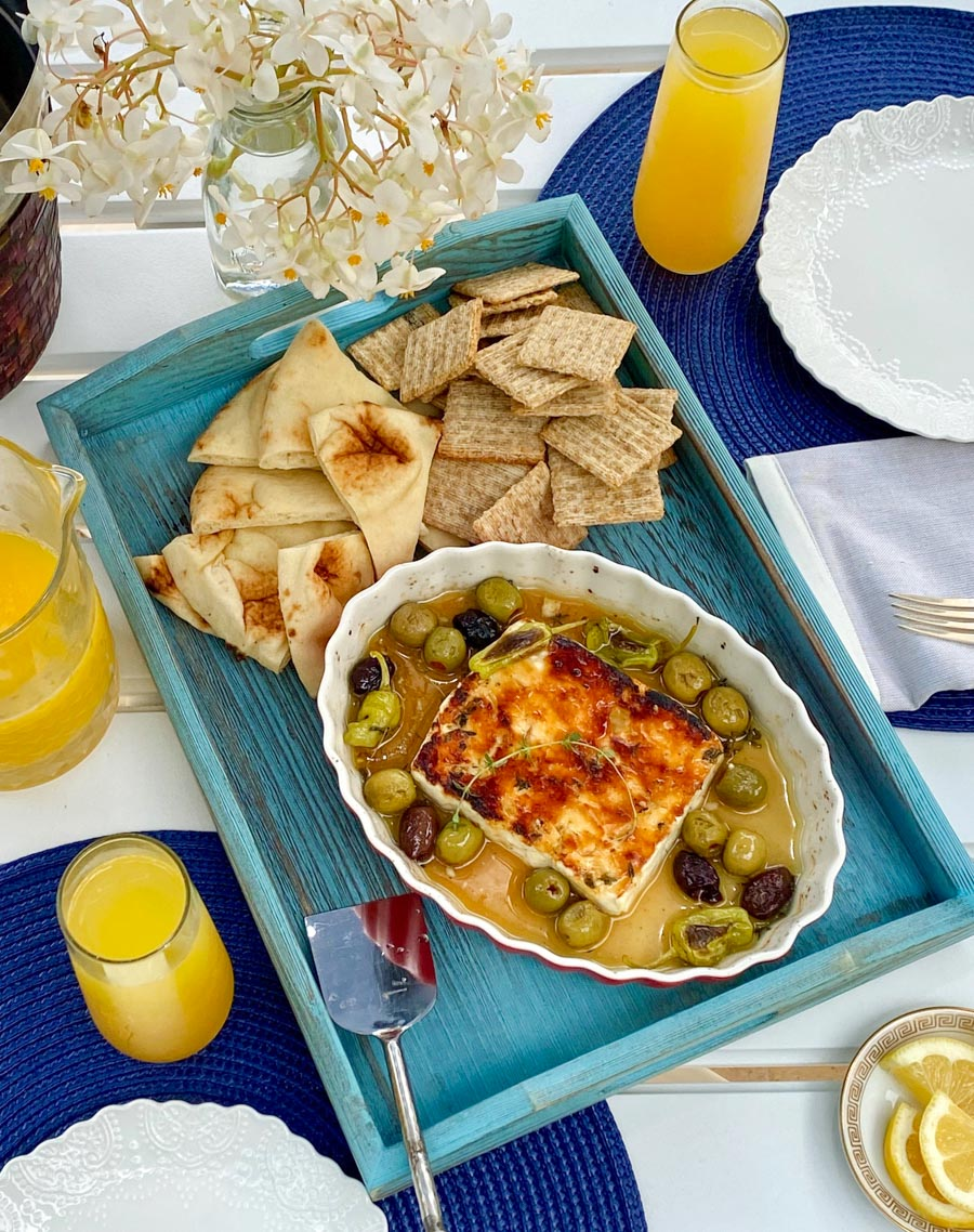 Baked Feta Cheese on a blue tray with crackers and pita bread