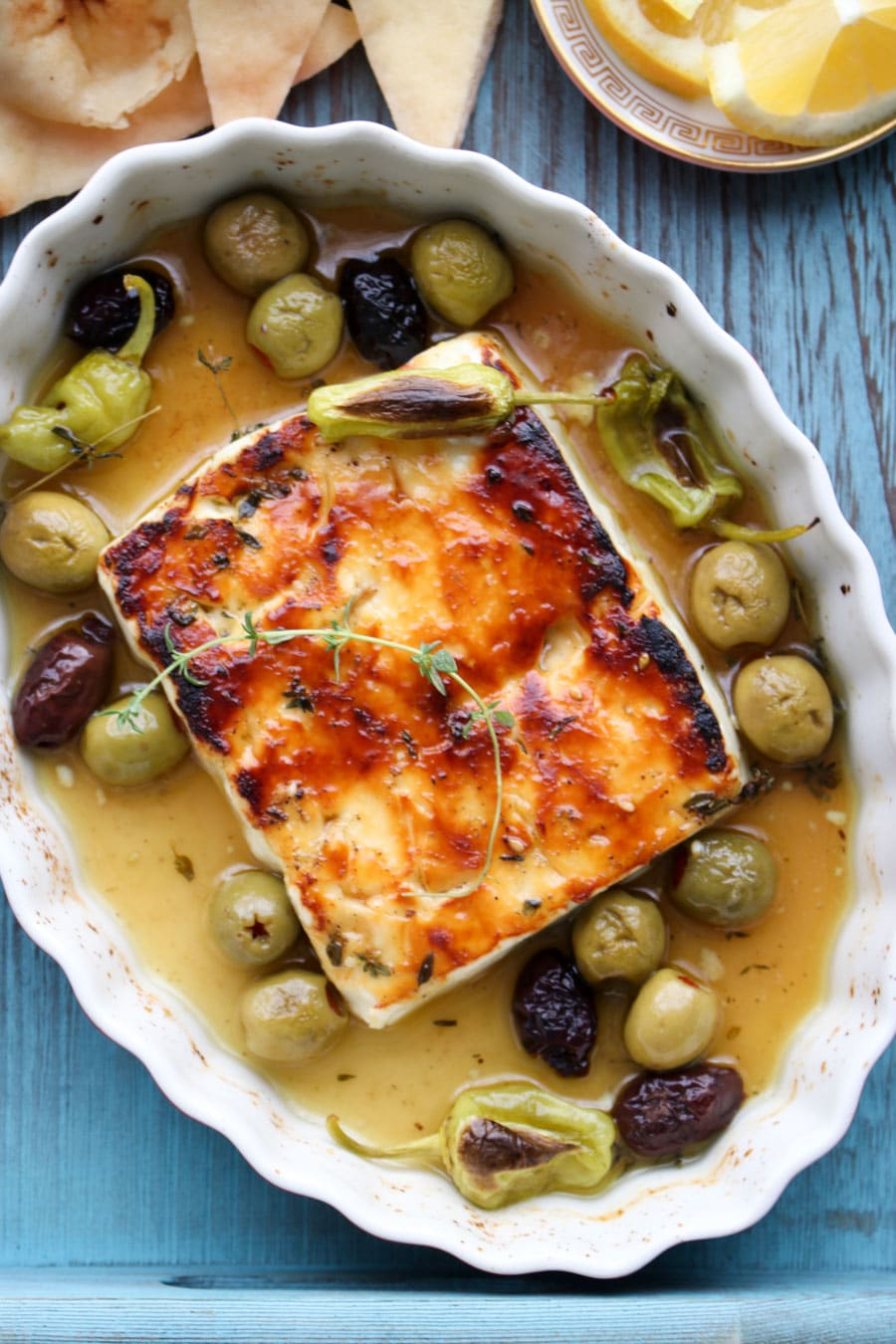 Baked feta in baking dish with olive and olive oil