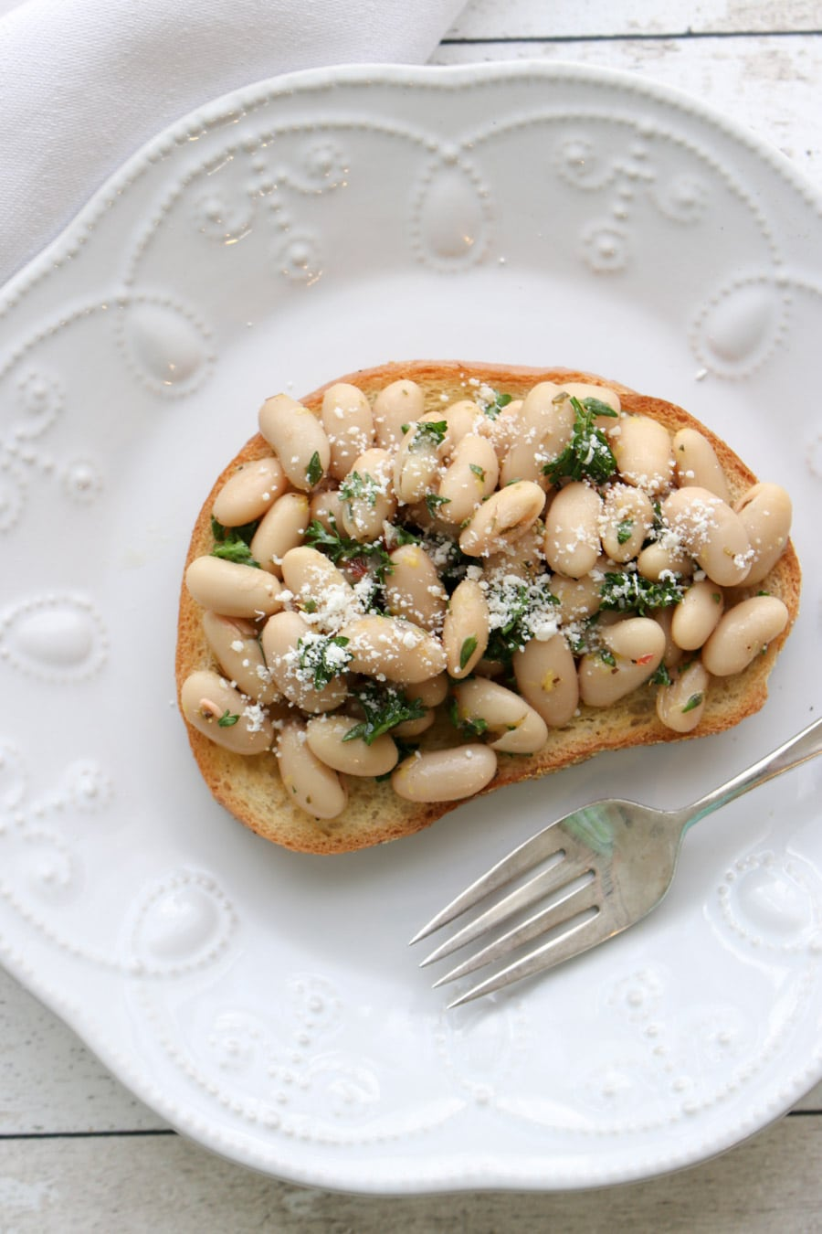 White Bean Salad piled high on a piece of toast on a plate