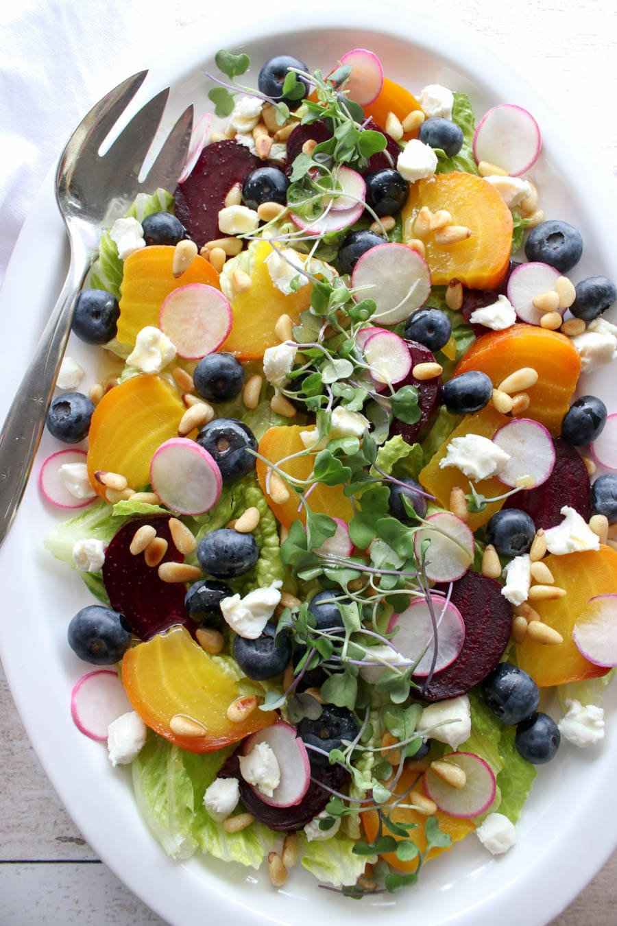 Large white platter with roasted beet salad with goat cheese