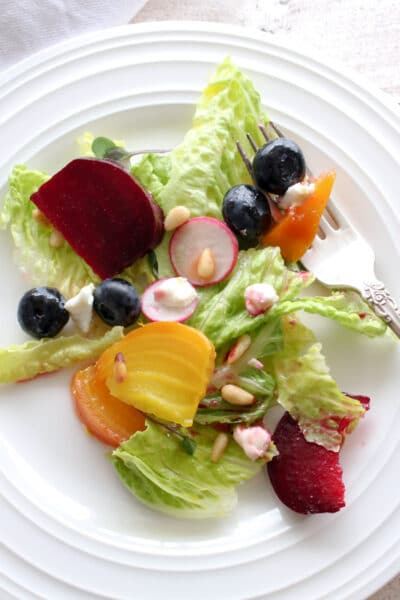 Beet salad on a white plate with a fork