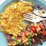 A plate of steak with tomato corn salsa and rice pilaf on the side
