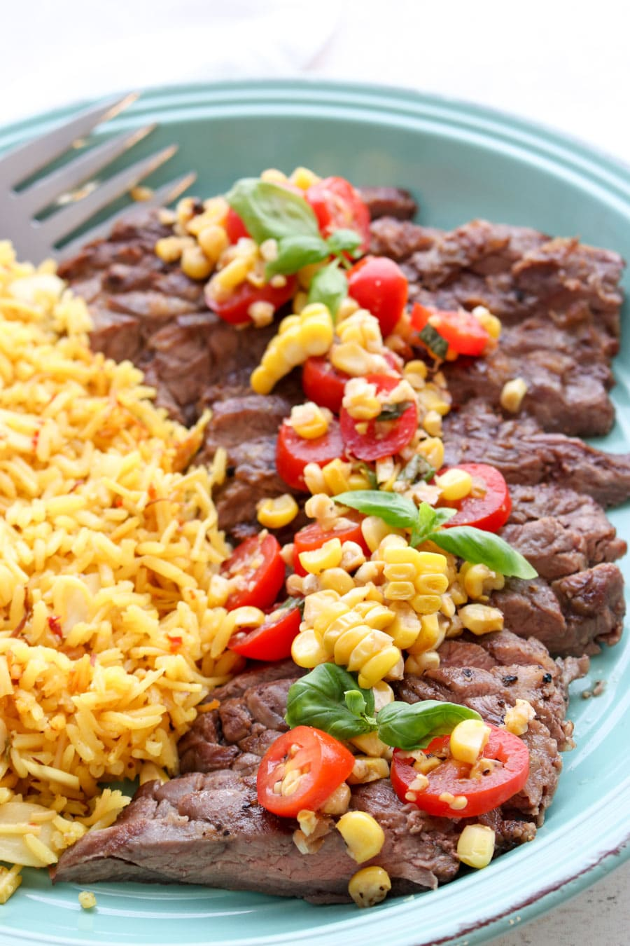 Platter of skirt steak with tomato corn salsa and a side of yellow rice