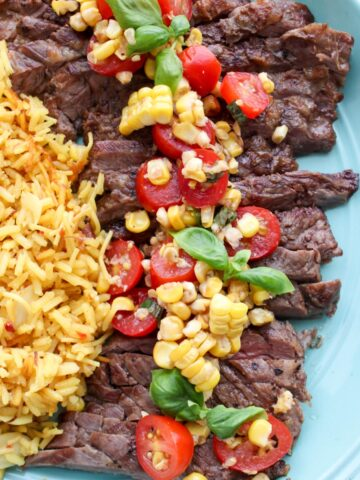 Platter with skirt steak topped with tomato corn salsa
