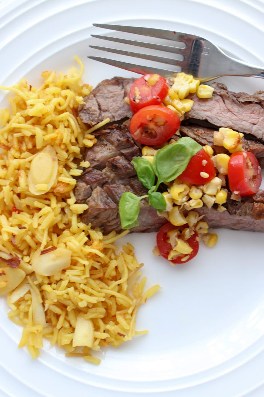 plate of skirt steak topped with salsa with a side of yellow rice