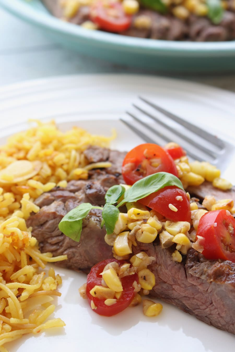 1 serving of skirt steak with tomato corn salsa on a white plate