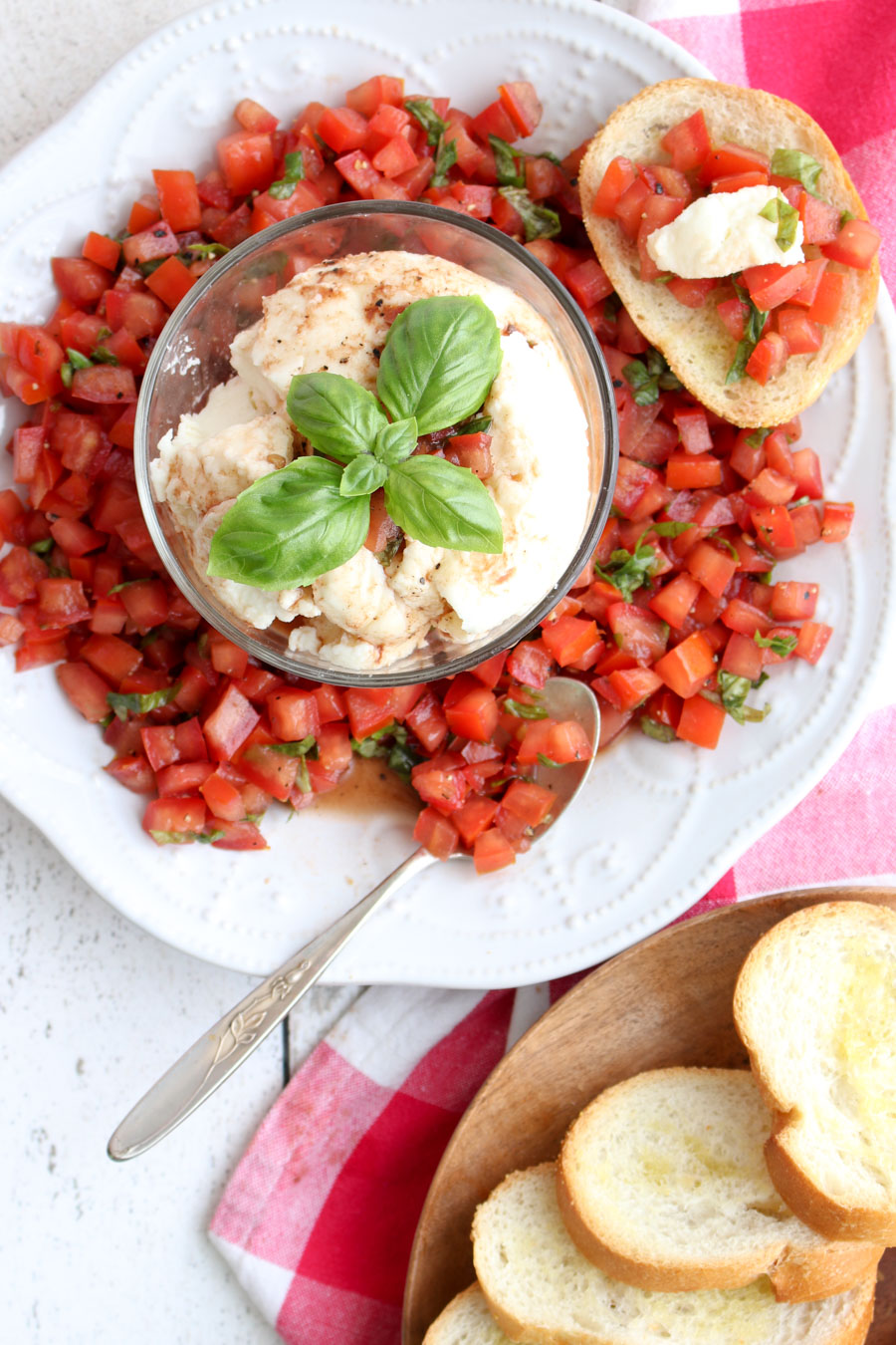 A plate of bruschetta with a bowl of fresh mozzarella in the center and toast on the side