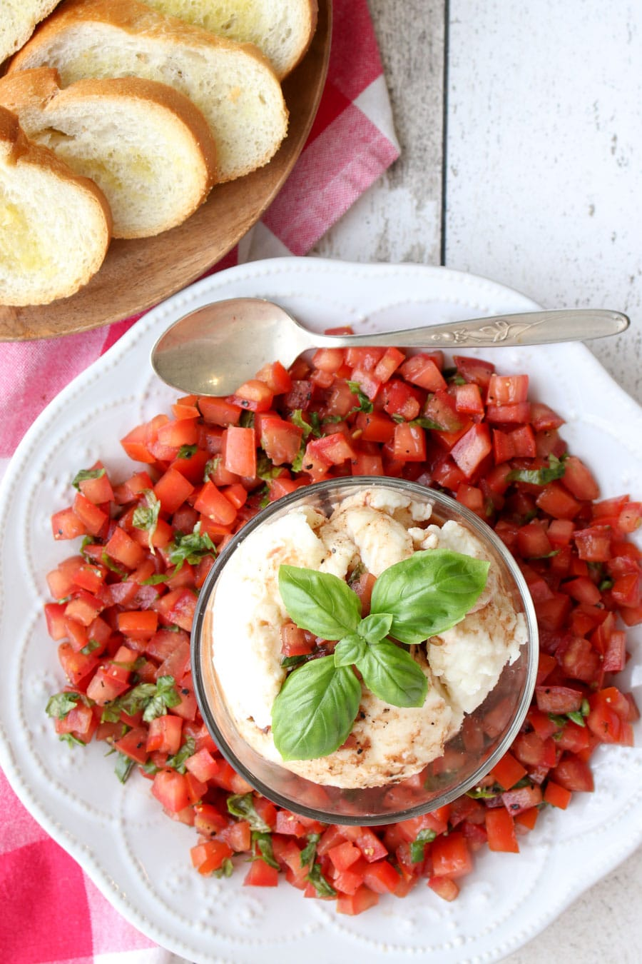 a platter of bruschetta with mozzarella cheese and toast on the side