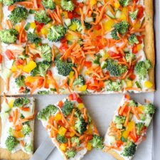 Veggie pizza on a sheet pan with three square pieces cut out