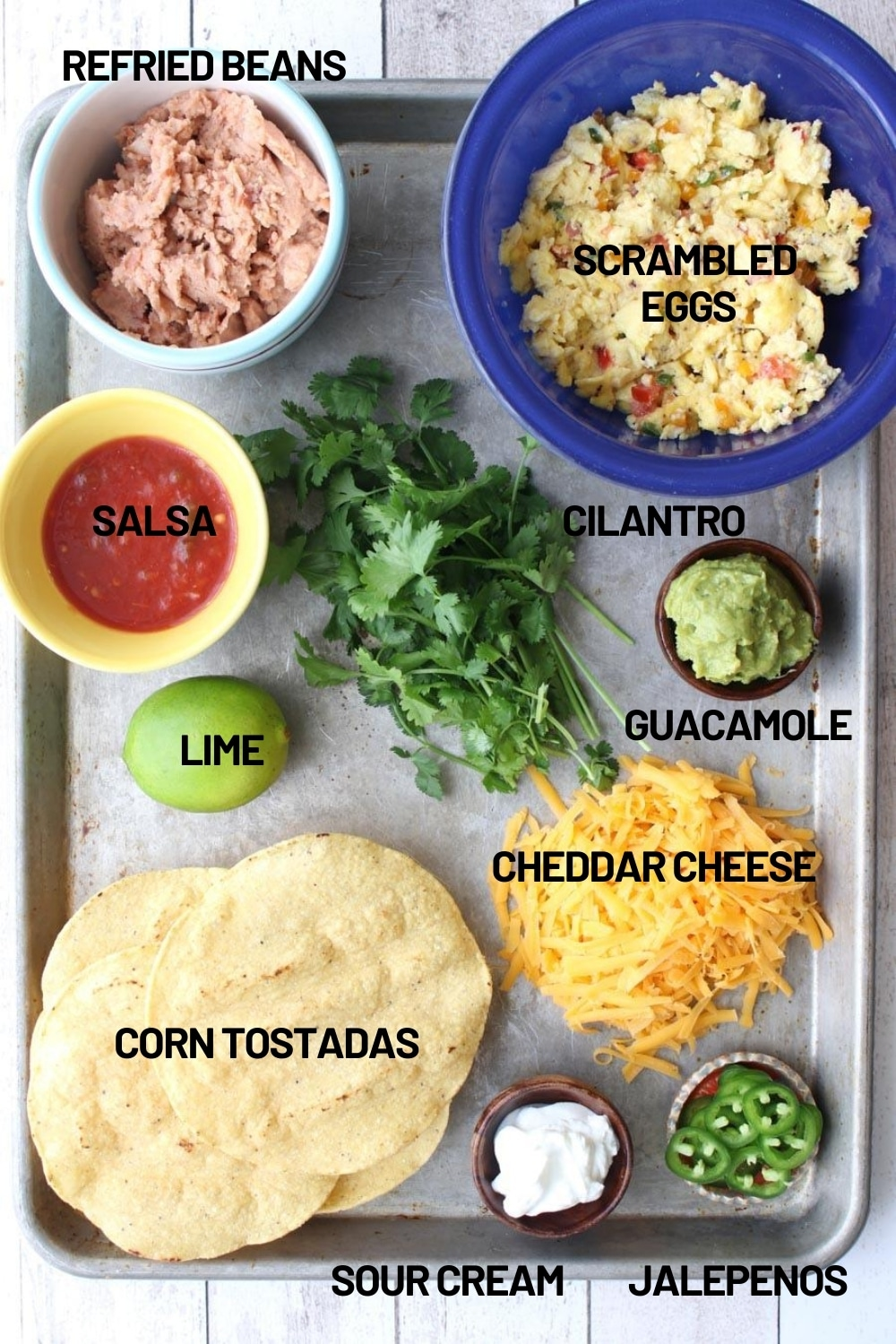 All of the ingredients needed to make huevous rancheros on a cookie sheet