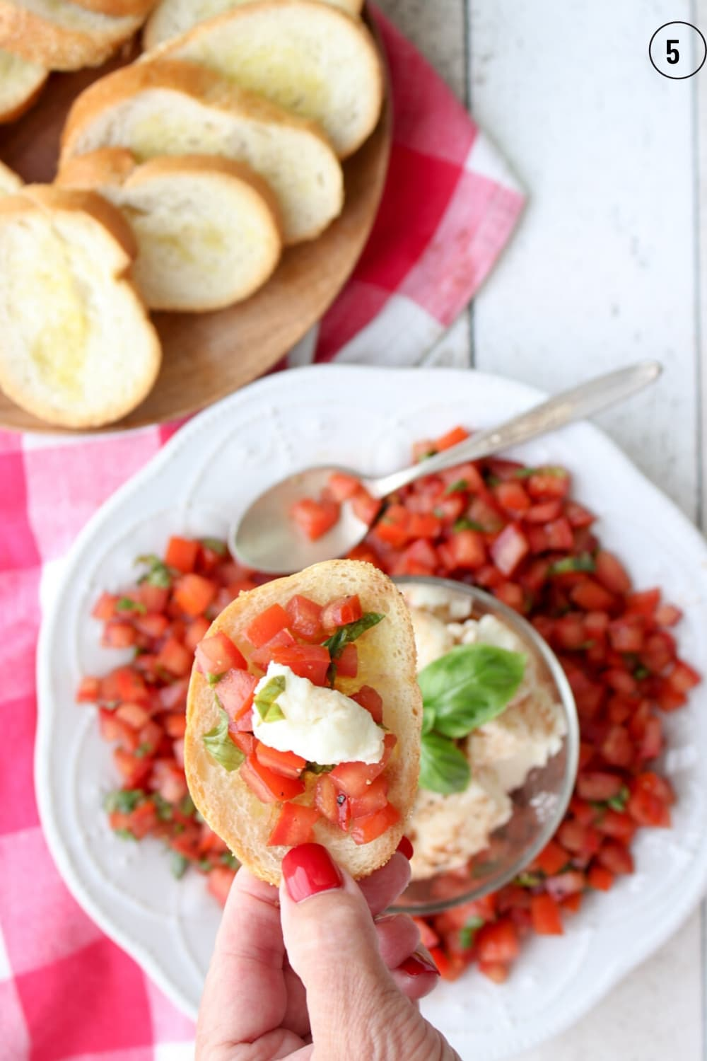 A hand holding a piece of toast topped with tomato bruschetta and cheese