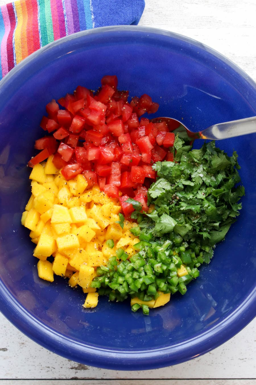 Blue bowl with all of the prepared ingredients to make mango salsa