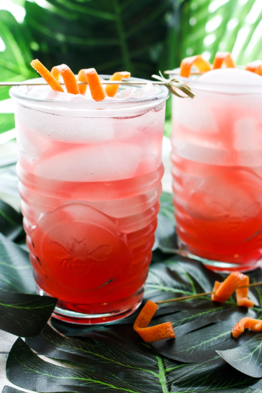 two glasses filled with pink cocktail sitting on big green leaves