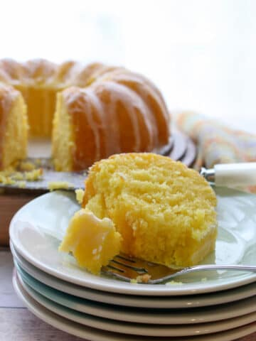 slice of lemon cake on a stack of plates with whole cake in background