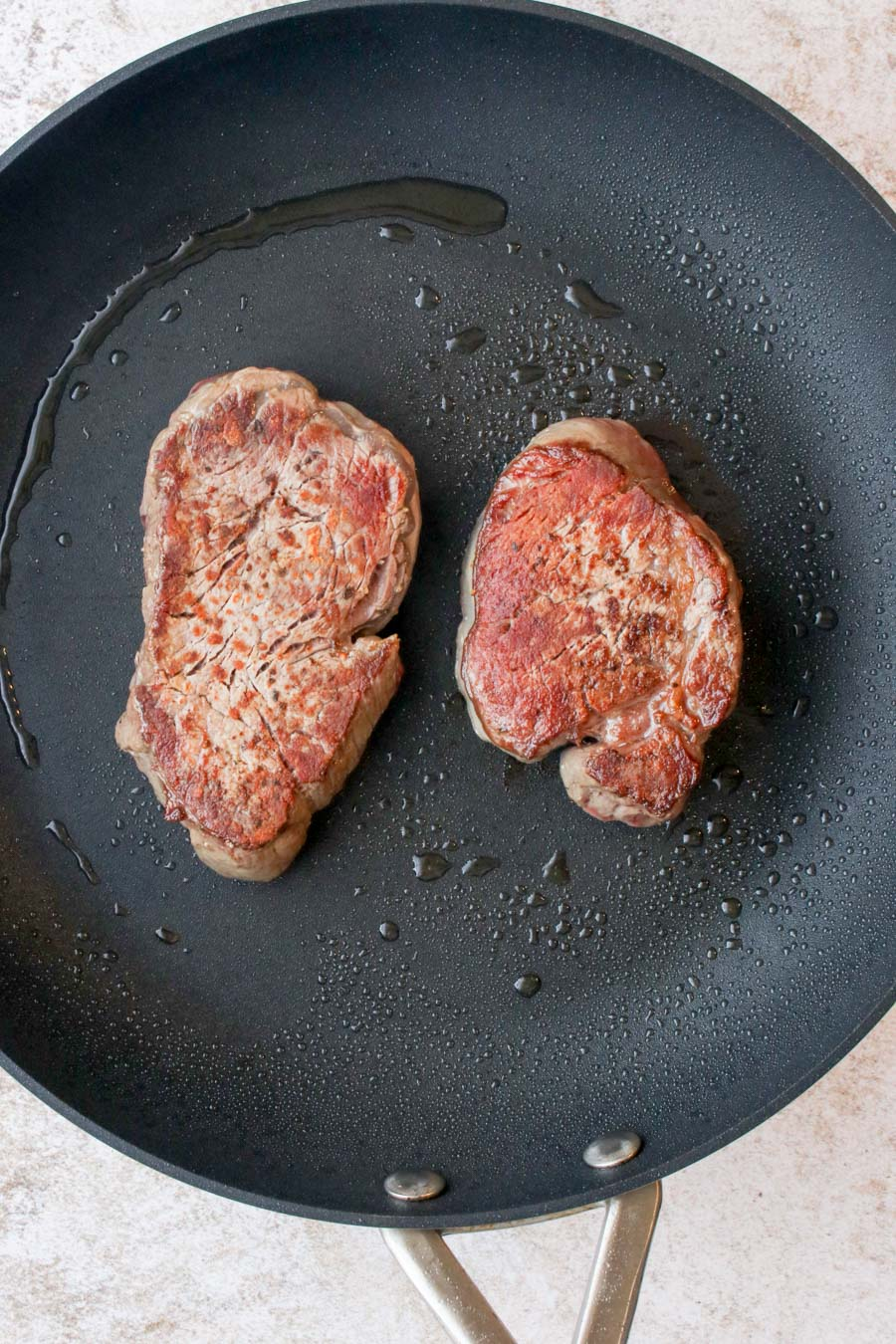 two filet steaks searing in a skillet