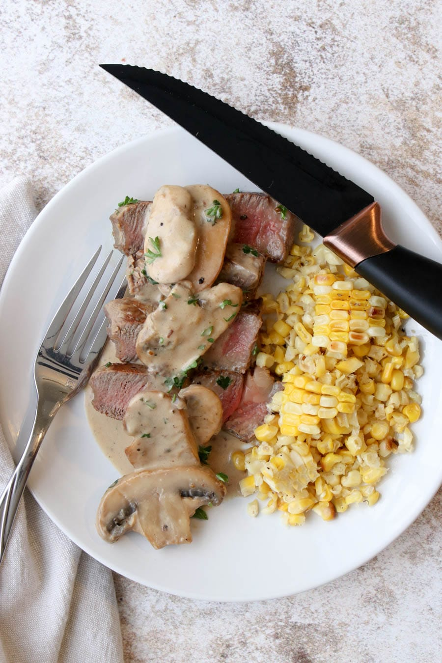 a white plate with slices of steak covered with a mushroom cream sauce and corn on the side.
