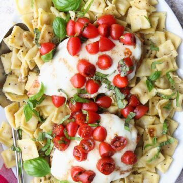 White platter filled with ravioli topped with chicken, cheese tomatoes and basil