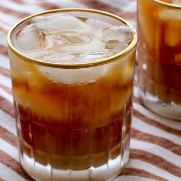 Glass of iced Irish Coffee with a striped background