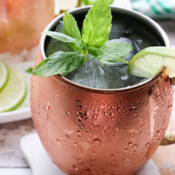 close up of a copper mug filled with ice, a drink and garnished with fresh mint