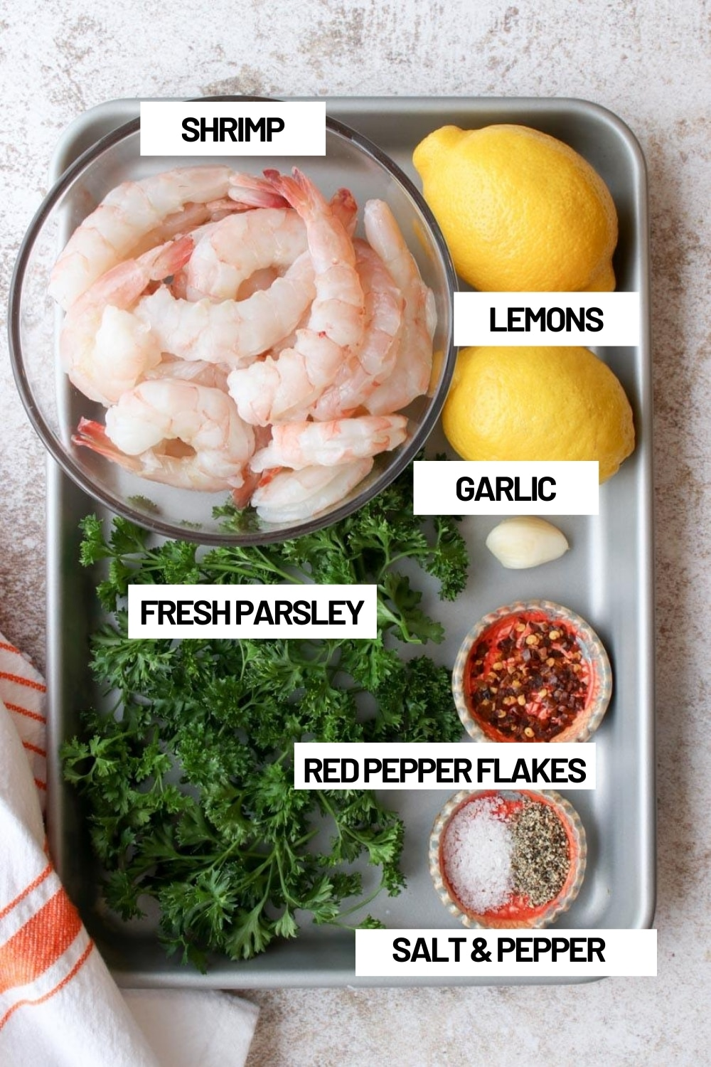 Cookie sheet with all of the ingredients needed to make grilled shrimp skewers
