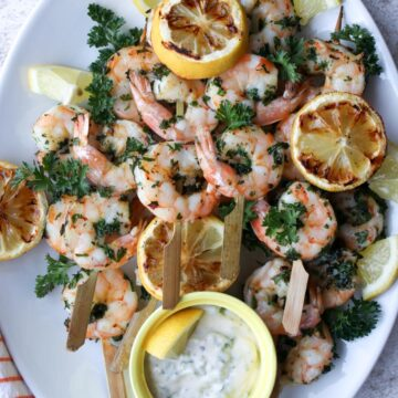 white platter with shrimp skewers and grill lemons on it with a side of white dipping sauce