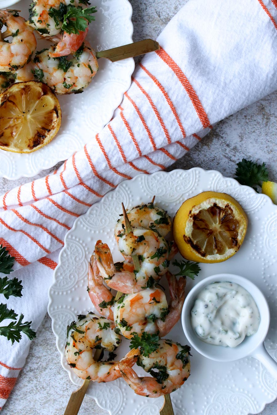 White plate with two shrimp skewers, a grilled lemon half, and some white sauce
