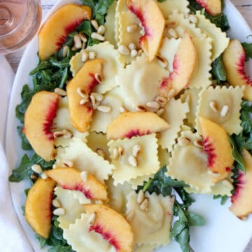 White platter with ravioli, arugula, peaches