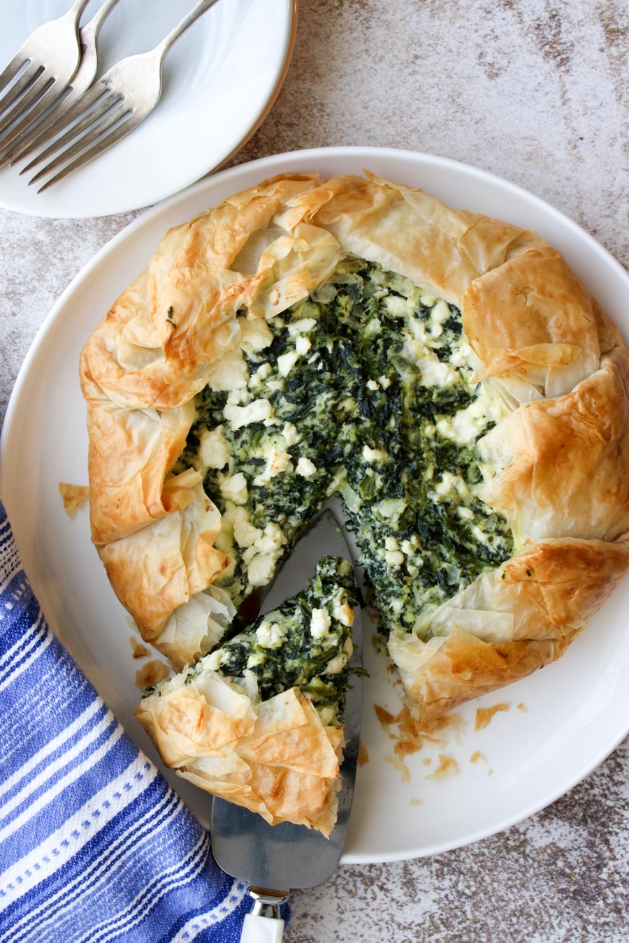 Spinach galette on a white plate with one slice being cut out