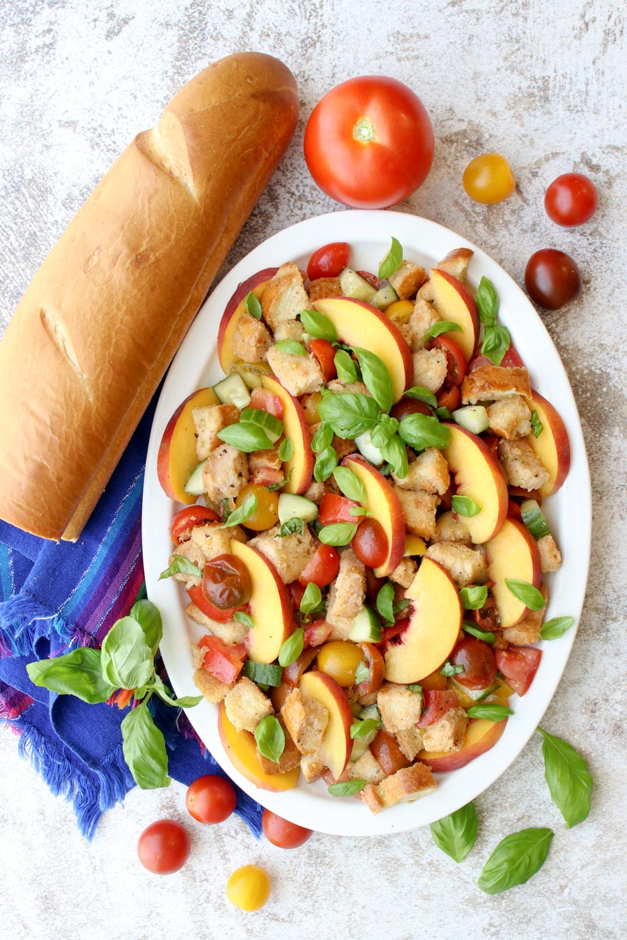 Bread salad on a white platter sitting next to a baguette