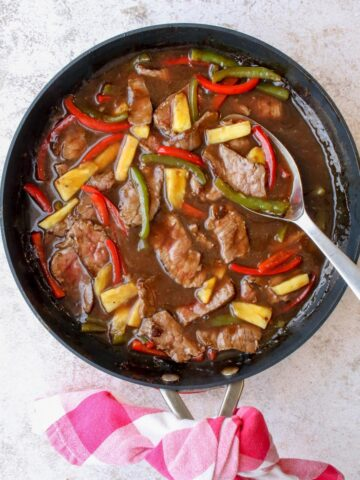 A skillet with cooked pepper steak