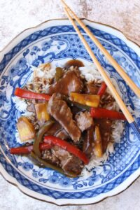 Blue plate with white rice and pepper steak and chop sticks on the side of plate