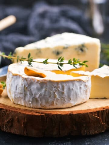 Brie Cheese wheel on a board with sprig of thyme on top