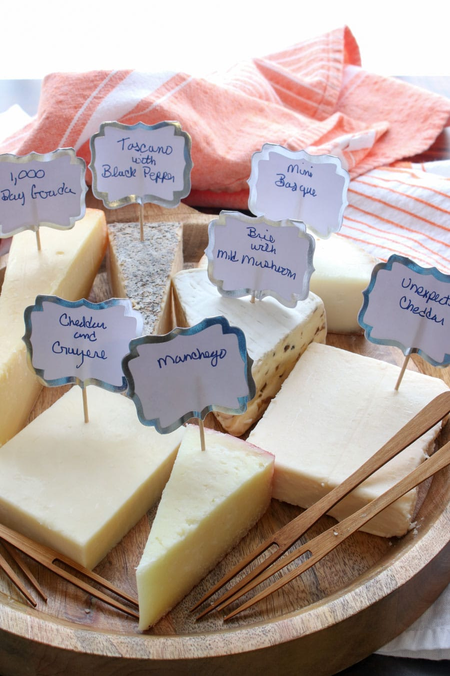 board with seven unwrapped cheeses with labels telling what they are